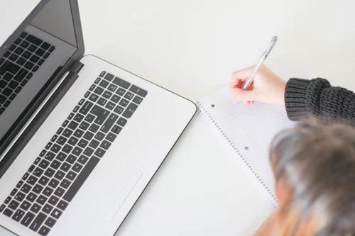 Persona sentada en un escritorio, con un bloc de notas y una computadora portátil abierta.