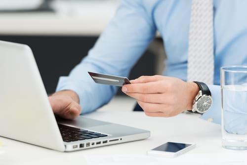 Empresario realizando transacciones en línea con tarjeta de crédito