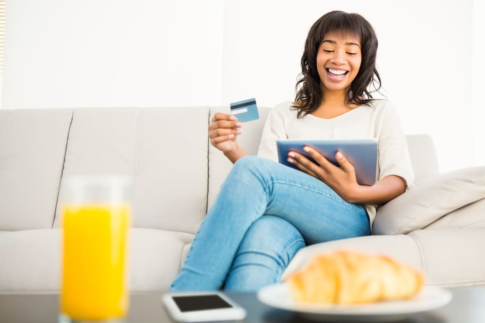 Casual woman using tablet while holding a card at home