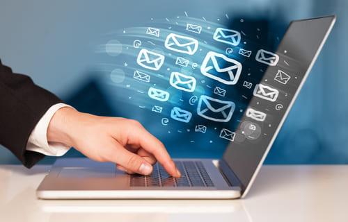 Portátil abierto con iconos de correo electrónico volando fuera de él