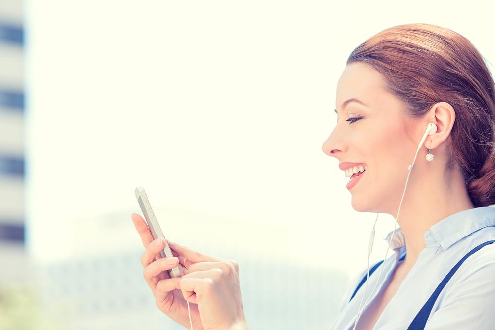 Mujer con audifonos sosteniendo un teléfono fuera de un conjunto de edificios.