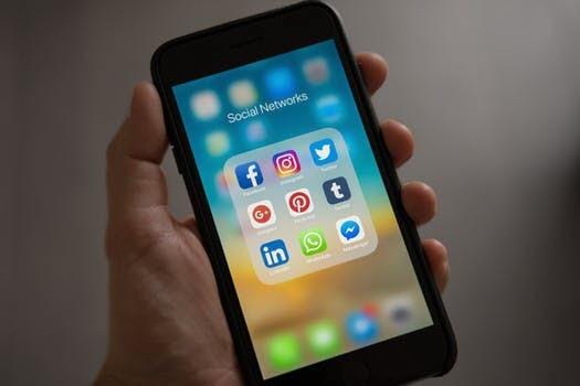 Mano sosteniendo un teléfono celular, con iconos de redes sociales en la pantalla